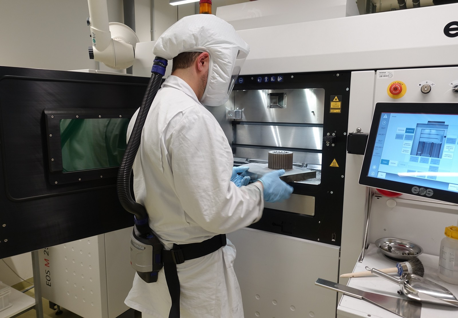 Ein Mitarbeiter mit dem Weltrekordhalter: Das weltgrößtes amorphe Metallbauteil aus dem 3D-Drucker.