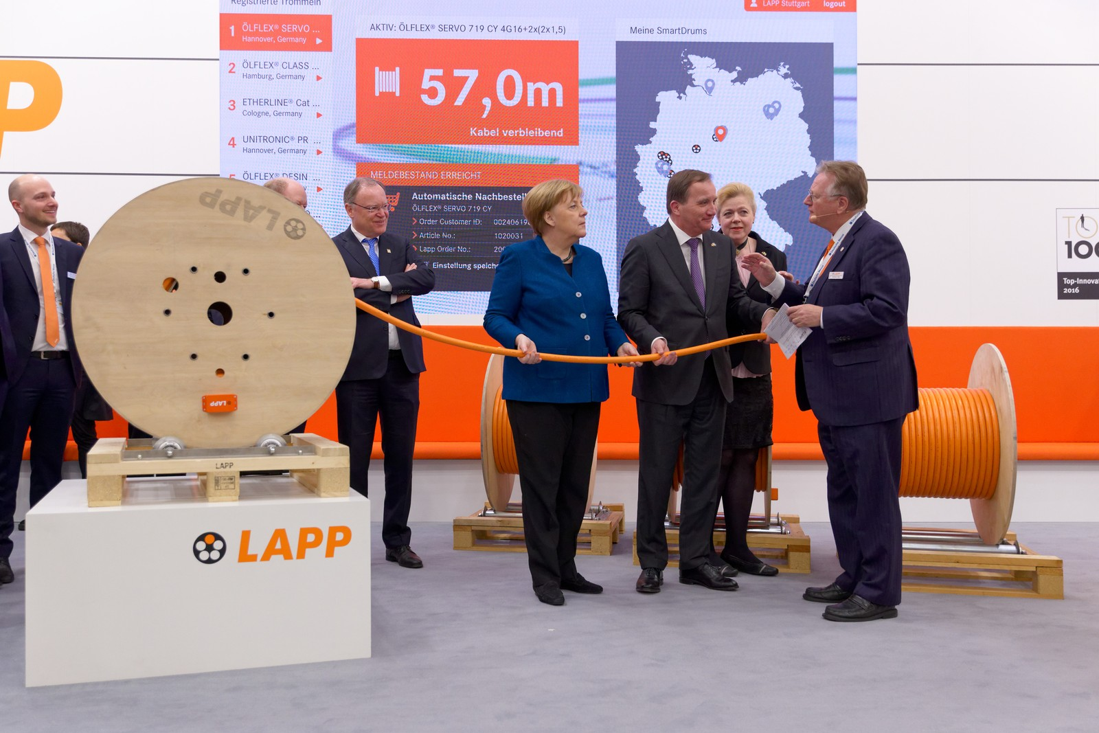 Andreas Lapp (r.) erklärt der Bundeskanzlerin Dr. Angela Merkel und dem schwedischen Ministerpräsident Stefan Löfven die digitalen Lösungen von Lapp.